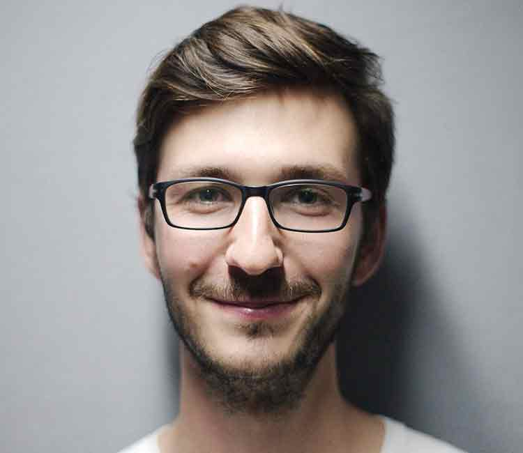 Man in a glasses is smiling